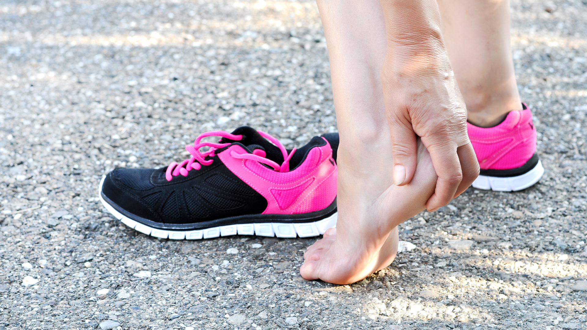 Woman holding heel struggling with achilles tendonitis