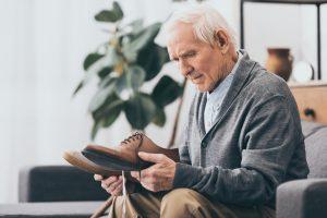 Senior man holding wide fitting comfort footwear shoe